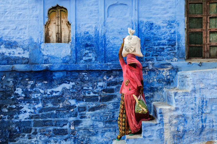 Woman in a red sari carrying a sack of rice down some steps