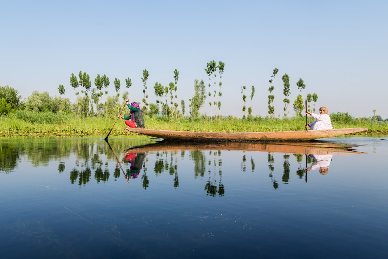 Women paddling a shikara on a lake in Kashmir
